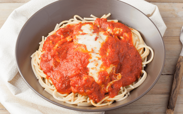 a beatiful plate of chicken parmigiana over spaghetti pasta