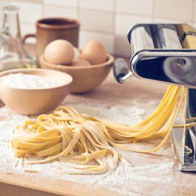 homemade fresh pasta and pasta machine on kitchen table