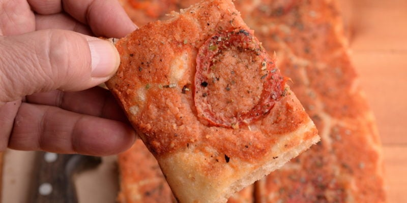 Breadcrumbs are sprinkled over the surface to make a crispy to layer to top off the pizza