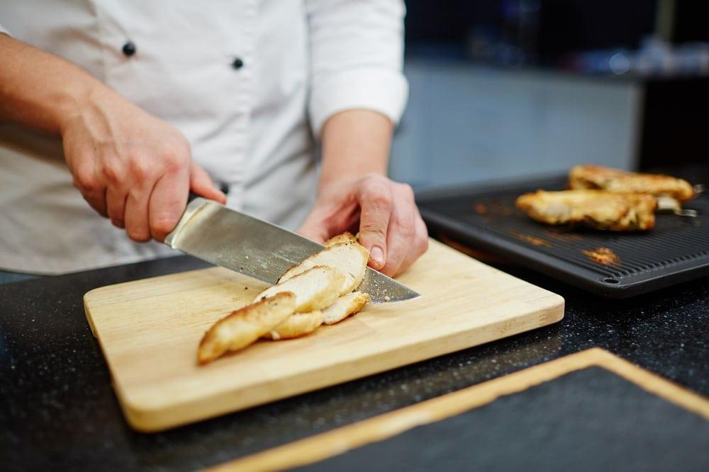 Chef cutting chicken